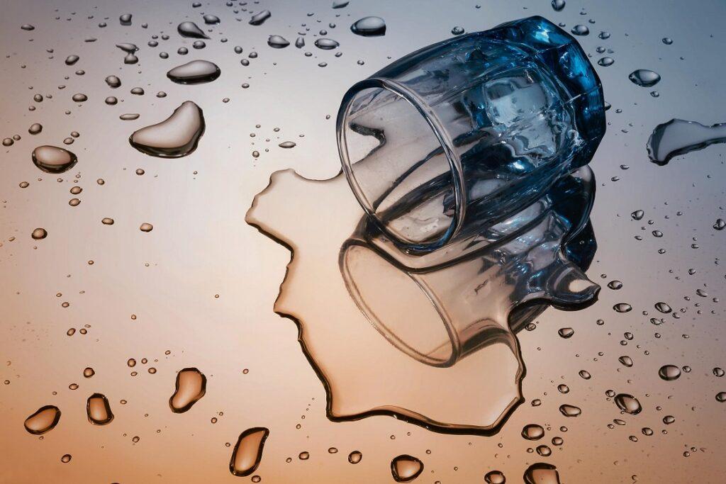 Vaso con alcohol derramado. El consumo de alcohol puede ser causa de diferentes tipos de trastornos